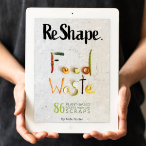 The photo of Kate Bartel holding the tablet with ReShape. Food Waste cookbook cover displayed ReShape. Food Waste is a zero-waste and vegan cookbook by Kate Bartel
